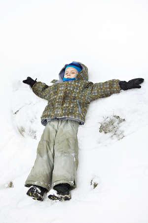 kindergartner: Llittle boy lies on snow and waving his arms Stock Photo