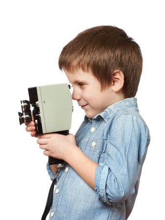 filming: Little boy cameraman filming with retro camera isolated Stock Photo