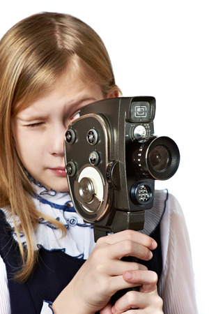 filming: Girl cameraman filming with retro camera isolated Stock Photo