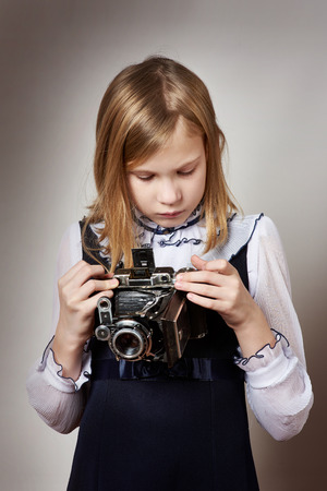 Girl photographer with retro camera photo