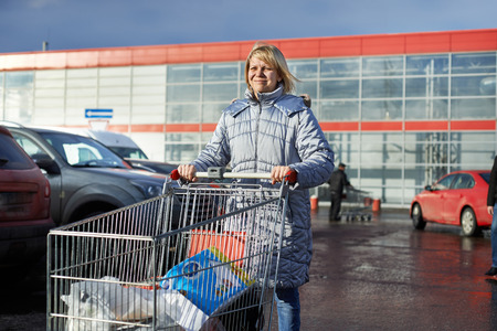 car retailer: Woman with shopping cart on parking near store