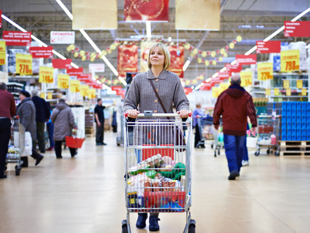 Women shopping in supermarket with cart 스톡 콘텐츠
