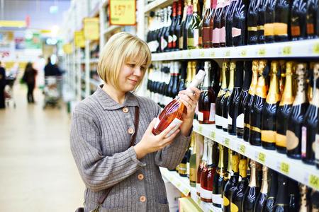 pink wine: Woman choosing pink wine in supermarket Stock Photo
