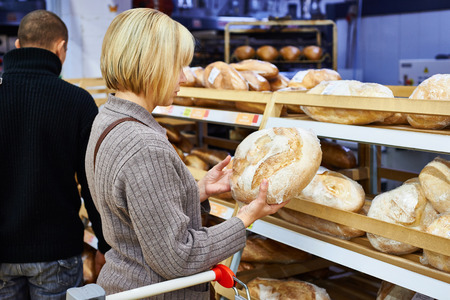 baking bread: Young woman chooses bread in the store