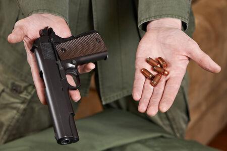 pistols: Soldier shows pistols and ammunition cartridges closeup