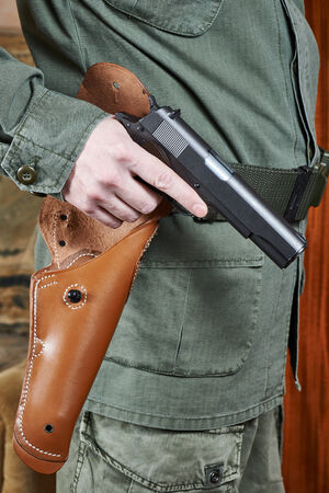 holster: Soldier in uniform holding a gun near holster Stock Photo