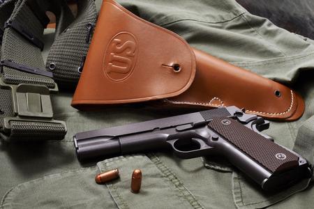 holster: pistol, holster and belt lie on military jacket closeup
