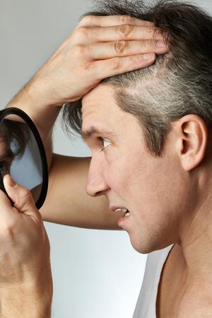 灰色の背景に彼の髪を見て鏡を持つ男