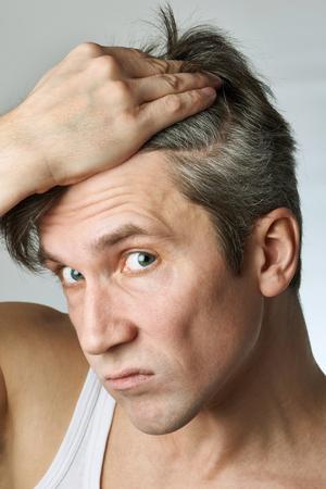 hombre calvo: Hombre con espejo mirando su pelo en el fondo gris