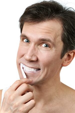 Man brushing his teeth on white background photo