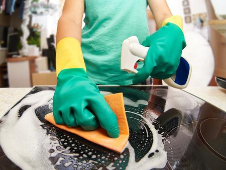 housekeeper: Estufa joven limpieza mujer en su cocina