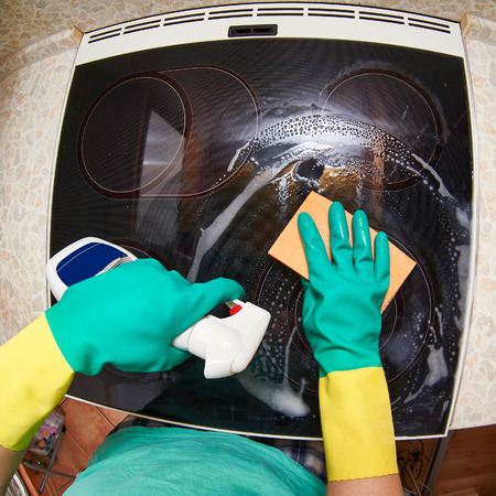 Young woman cleaning stove in her kitchen photo