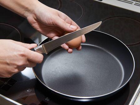 fried eggs: Woman preparing fried eggs for breakfast Stock Photo