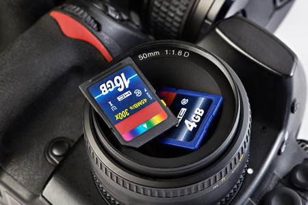 sd: Two SD memory flash card and DSLR camera close-up Stock Photo