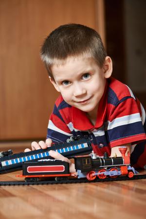 kindergartner: Little boy playing with railway lying on the floor Stock Photo