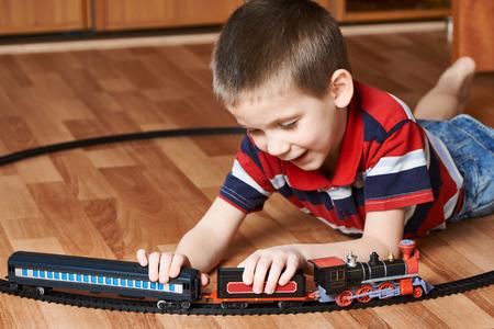 kindergartner: Happy little boy playing with railway lying on the floor