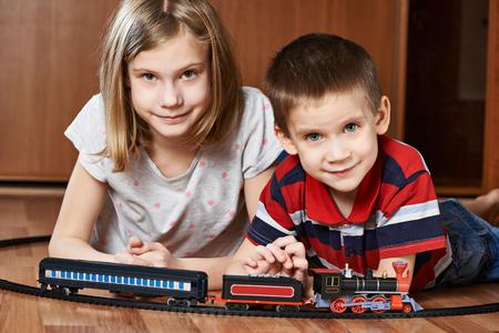 kindergartner: Sister and brother playing with railway lying on the floor Stock Photo