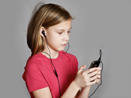 isolated on gray: Girl listening to music on your phone isolated gray