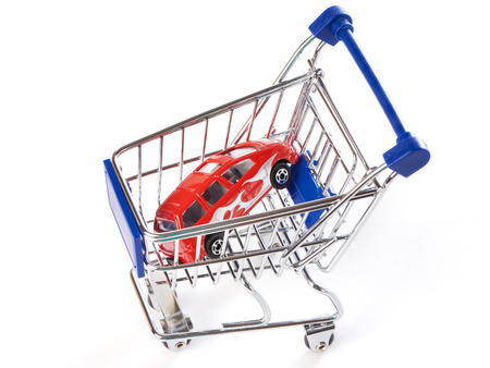 Shopping trolley with toy car isolated on white background photo