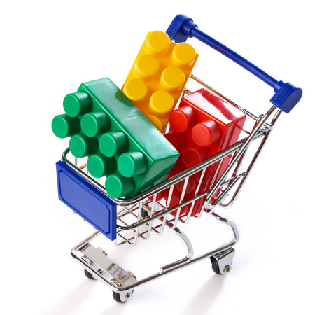 shopping trolley: Shopping trolley with toy colorful plastic blocks isolated