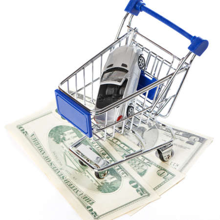 car retailer: Shopping trolley with money and toy car isolated on white background