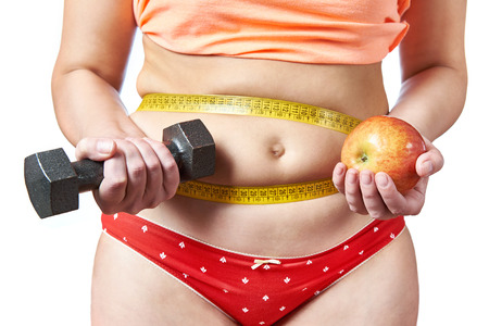 Woman with dumbbells and apple diet plans and sport activities photo