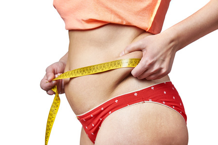 deposits: Woman measuring waist with a measuring tape and showing fatty deposits Stock Photo