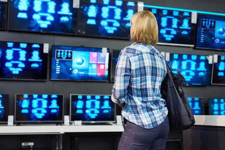 Blonde girl looks at LCD TVs in supermarket photo