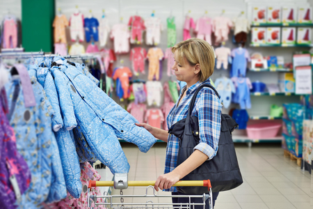 Beautiful woman chooses rompers in store photo