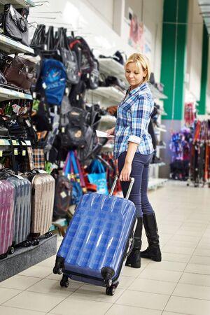 portmanteau: Beauty woman chooses suitcase in shop