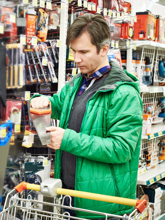 handsaw: Man Buying Handsaw In Hardware Store Stock Photo