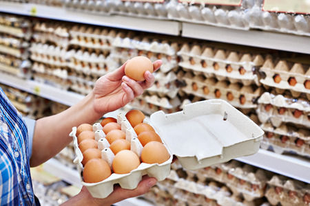 checking ingredients: In the hands of a woman packing eggs in the supermarket Stock Photo