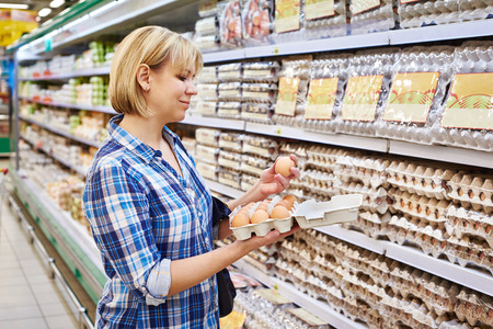 Woman chooses packing eggs in the supermarket