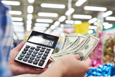 considers: Housewife with dollars and calculator considers costs in the store