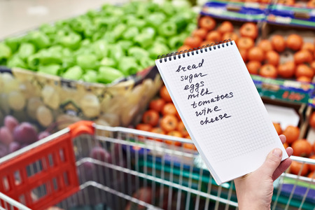 carts: Shopping list in the hands of a woman in a supermarket