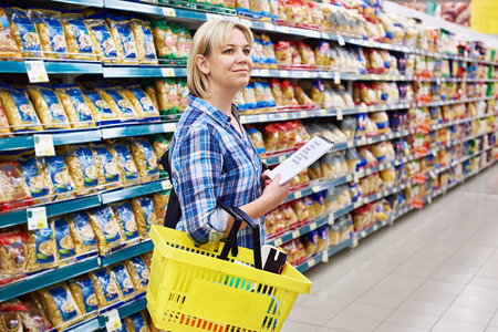 Счастливая женщина домохозяйка с список покупок в супермаркете Фото со стока