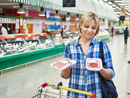 Woman buys a meat in the supermarket Banque d'images
