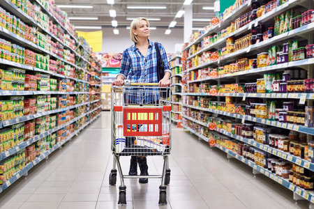 comprando: Las mujeres ama de casa con el carro de compras en el supermercado