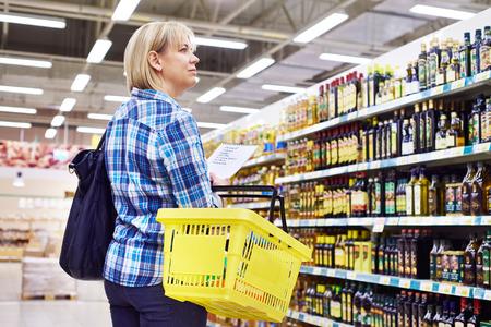 aceite de oliva: Mujer ama de casa con la lista de compras en el supermercado