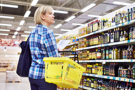 food shelf: Woman housewife with list shopping in supermarket