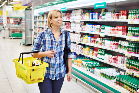 shopping list: Women housewife with yellow basket shopping in supermarket Stock Photo