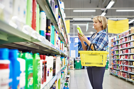 Woman chooses shampoo in cosmetics department in supermarket