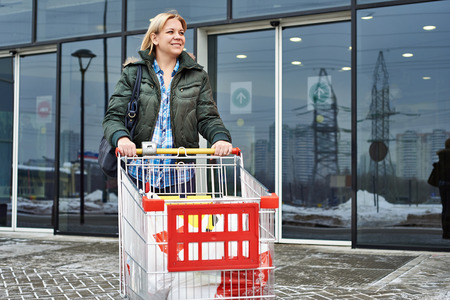 woman shopping cart: Woman with shopping cart exits the supermarket Stock Photo