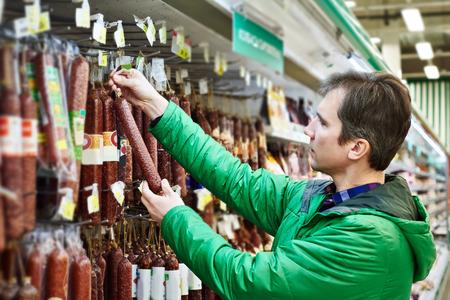 Человек покупает сырокопченых колбас в супермаркете