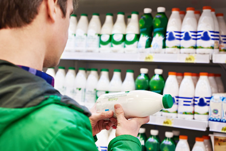 food shelf: Man shopping milk in grocery store