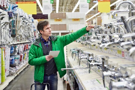 Man shopping for bathroom equipment in DIY shop Banco de Imagens