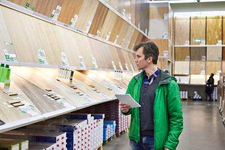 Человек торговый ламинат в магазине DIY для строительства