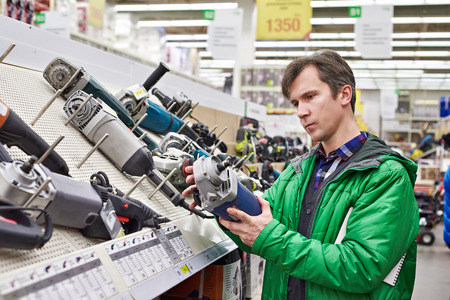 Man shopping for sander in hardware store close-up Imagens