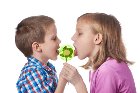 Girl and boy eating a lollipops isolated photo