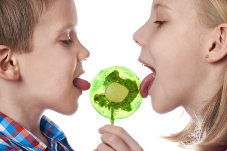 Girl and boy eating a lollipops isolated